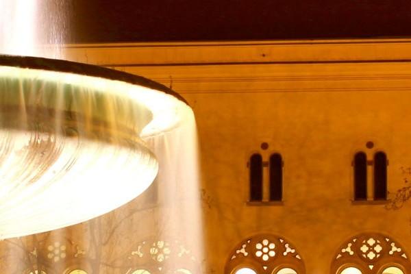 Weiß strahlender Brunnen und das leuchtende LMU Hauptgebäude bei Nacht.