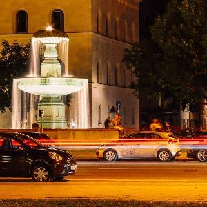 Die Ludwigsstraße bei Nacht, auf welcher Autos am beleuchteten Brunnen der LMU vorbeifahren.