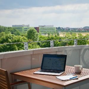 Aufnahme einer Terrasse und einem Tisch, auf dem eine Tasse und ein Laptop stehen