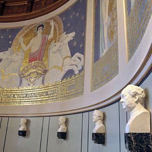 Bild der großen Aula im LMU Hauptgebäude mit einigen Mamor Büsten und einem großen Wandornament