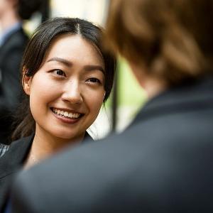 Nahaufnahme einer lächelnden Frau im Gespräch bei einem Career Event der LMU.