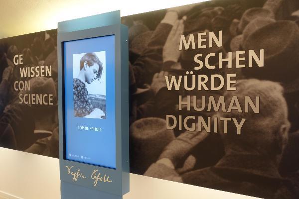 Eine Wand mit der Aufschrift Menschenwürde in verschiedenen Sprachen in der weissen Rose Gedenkstätte im Hauptgebäude der LMU.