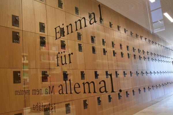 Eine Glaswand des Philologicums der LMU. Dahinter sind die Schließfächer zu sehen.