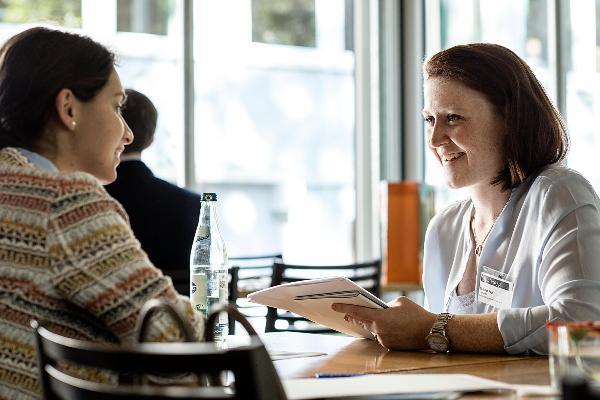 Zwei Frauen sitzen an einem Tisch und führen ein Jobinterview.