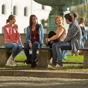 Studierende sitzen am Brunnen vor dem Hauptgebäude der Universität.