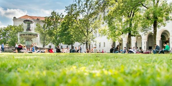 Bild der Graßfläche vor dem LMU Hauptgebäude auf der Studierende sitzen und das Wetter genießen.