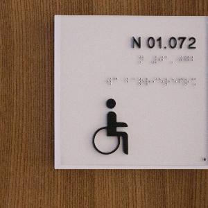 Schild mit einer Raumnummer und einer Grafik eines Rollstuhlfahrers