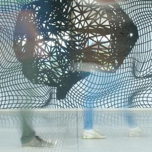 Personen, welche nur verschwommen zu sehen sind, laufen vor eiinem Kunstwerk am Eingang des BMC