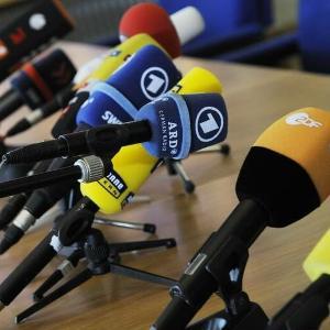 Tischmikrofone verschiedener Sender bei einer Pressekonferenz