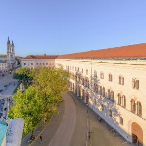 Das Hauptgebäude der LMU von der Seite. Im Hintergrund ist die Ludwigskirche zu erkennen