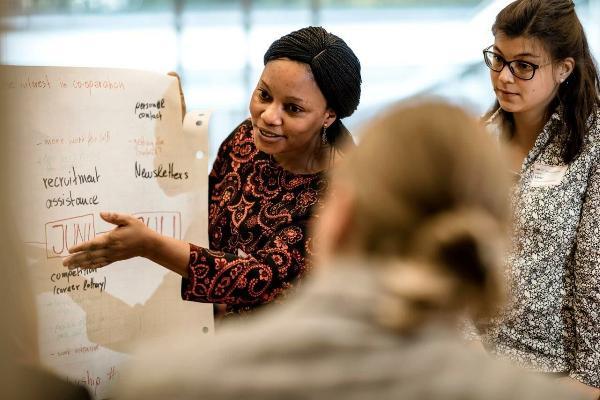 Frau erklärt in einem Seminar etwas anhand einer Flipchart.