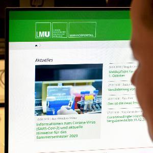 Frau vor Computer informiert sich im Serviceportal der LMU