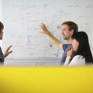 Personen stehen an einer Tafel und erklären sich gegenseitig etwas.