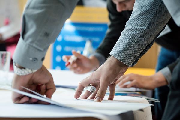 Student stützt seine Hände auf einem Plakat ab.