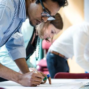 Ein Alumnus zeichnet etwas auf ein Plakat während eines Workshops