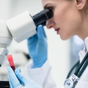Eine Person mit Laborkittel und Gummihandschuhen sieht durch ein Mikroskop