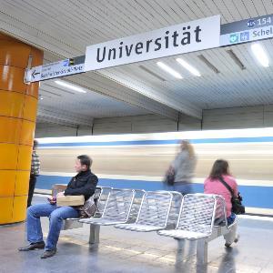 Personen warten an der U-Bahn Haltestelle der LMU.