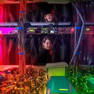 Prof. Dr. Monika Aidelsburger steht hinte einem großen Versuchsaufbau der in farbigem Licht strahlt
