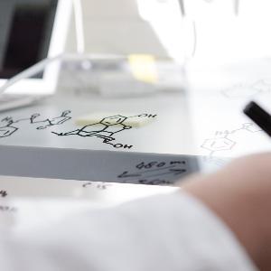 Zu sehen ist eine schreibende Hand und ein kleiner Bildschirm im Hintergrund.