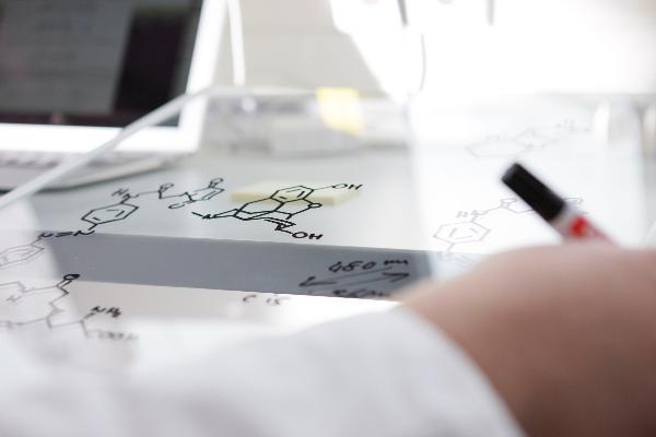 Eine Hand zeichnet Moleküle, im Hintergrund ist ein Bildschirm zu sehen