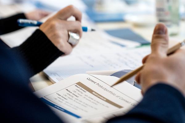 Seminarteilnehmer gehen ein Skript in Papierform durch.