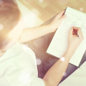 Eine Person wird von oben beim Ausfüllen eines Formulars gezeigt.