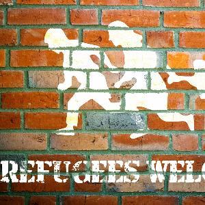 Grafitti mit der Botschaft Refugees welcome auf einer Mauer.