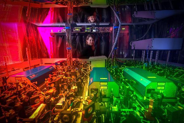 Prof. Dr. Monika Aidelsburger steht hinte einem großen Versuchsaufbau der in farbigem Licht strahlt.