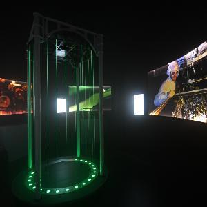 Ein dunkler Raum in einer Ausstellung, mit einem Exponat in der Mitte.