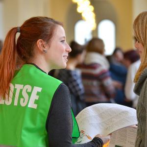 Eine Helferin erklärt einer Studentin etwas auf dem LMU Campustag.