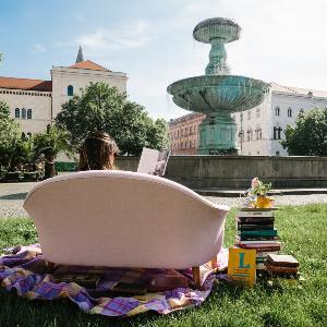 Eine Studentin liest auf einer Couch vor dem Brunnen am Geschwister-Scholl-Platz ein Buch.