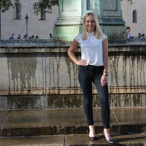 Foto einer Studentin vor dem Brunnen der LMU am Geschwister-Scholl-Platz.