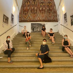 Studierende sitzen mit der Dozentin Krämder de Huerta auf einer Treppe im Museum Fünf Kontinente
