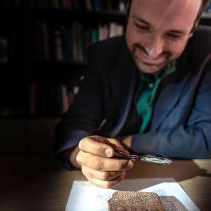 Professor Enrique Jiménez sitzt am Tisch und betrachtet einen Gegenstand in der Hand.