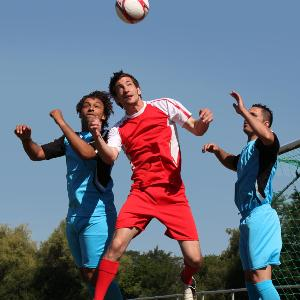 Drei Personen spielen Fußball.