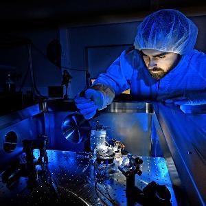 Ein Mann mit Schutzanzug macht einen Versuch in einem Physik Labor