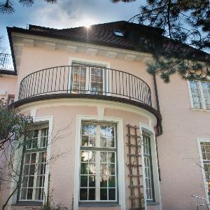 Ein LMU Gebäude mit runden Balkon und Bäumen davor