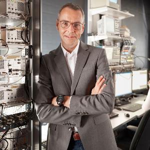 Prof. Dr. Immanuel Bloch steht vor Datenträgern in einem großen Büro.