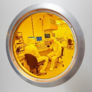 Blick in ein geschlossenes Labor, in welchem zwei Forscher mit Schutzanzügen sitzen.