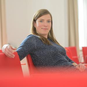 Dr. Antonia Misch sitzt in einem Raum mit roten Stühlen