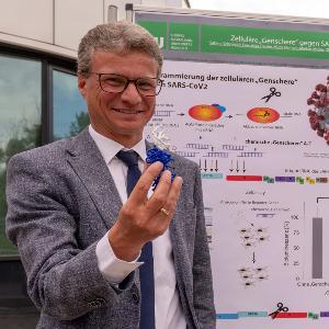 Staatsminister für Wissenschaft und Kunst Bernd Sibler vor einer Stellwand bei der LMU München im Genzentrum