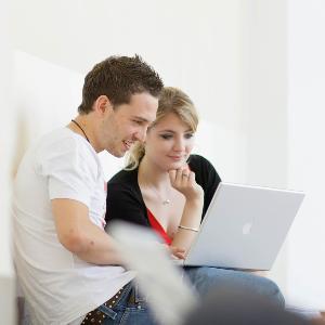 Studierende sitzen vor einem Laptop und unterhalten sich.