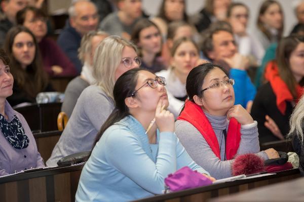 Studierende und Besucher nebeneinander in einer Vorlesung.