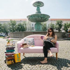 Eine Studentin liest auf einer rosa Couch vor dem Brunnen am Professor-Huber-Platz ein Buch.