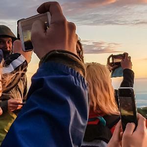 Einige Personen fotografieren den Sonnenaufgang auf dem Gipfel des Berges Geigelstein.