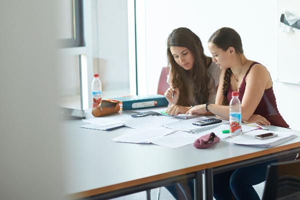 ZWei Studentinnen sitzen an einem Tisch und lernen gemeinsam.