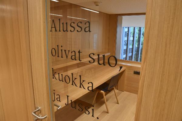 Eine Glaswand des Philiogicums der LMU. Dahinter ein Einzelraum zum Lernen.