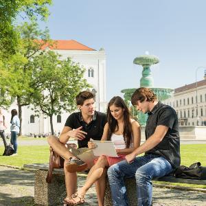 Studierende unterhalten sich auf einer Bank am Geschwister-Scholl-Platz.