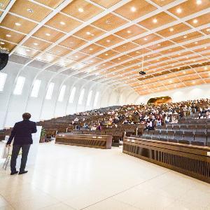 Blick in einen großen Hörsaal voller Studierenden während einer Vorlesung.