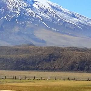 Blick auf eine Holzbrücke inmitten der Landschaft von Ecuador mit einem großen Berg im Hintergrund.
